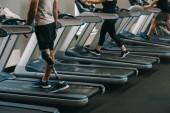 Erschossener Mann mit künstlichem Bein läuft mit anderen Menschen auf Laufbändern in Fitnessstudio