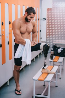 happy young sportsman with artificial leg standing at changing room of swimming pool