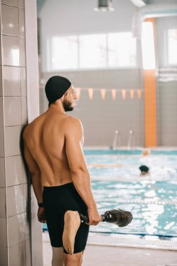 rear view of swimmer standing at poolside of indoor swimming pool and holding his artificial leg
