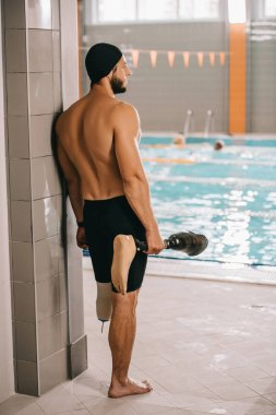 rear view of young swimmer standing at poolside of indoor swimming pool and holding his artificial leg
