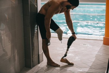 handsome young swimmer standing at poolside of indoor swimming pool and taking off artificial leg