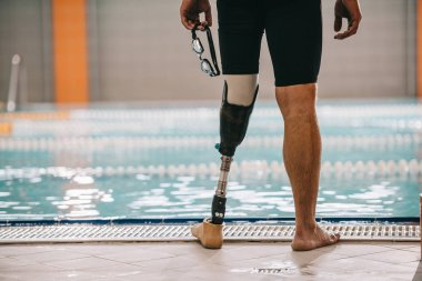 cropped shot of swimmer with artificial leg standing in front of indoor swimming pool and holding swimming goggles