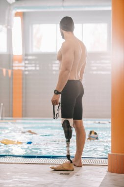 handsome young sportsman with artificial leg standing in front of indoor swimming pool
