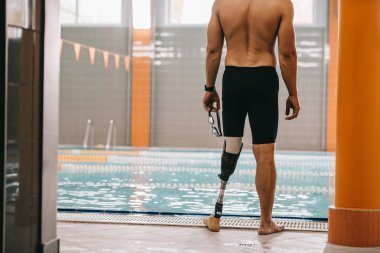 cropped shot of sportsman with artificial leg standing in front of indoor swimming pool