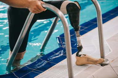 cropped shot of swimmer with prosthetic leg getting out of swimming pool