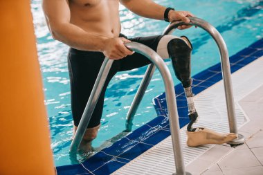 cropped shot of athletic swimmer with artificial leg getting out of swimming pool