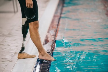cropped shot of fit swimmer with artificial leg standing on poolside at indoor swimming pool and checking water temperature