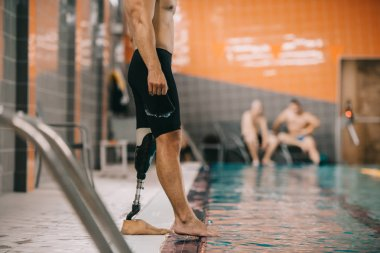 cropped shot of muscular sportsman with artificial leg standing on poolside at indoor swimming pool and checking water temperature