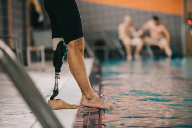 cropped shot of sportsman with artificial leg standing on poolside at indoor swimming pool and checking water temperature