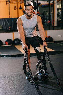 muscular young sportsman with artificial leg working out with ropes at gym