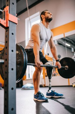 bottom view of young sportsman with artificial leg working out with barbell at gym