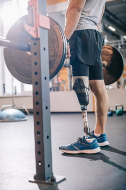 cropped shot of man with artificial leg working out with barbell at gym
