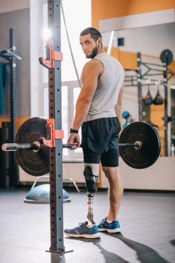 athletic sportsman with artificial leg working out with barbell at gym