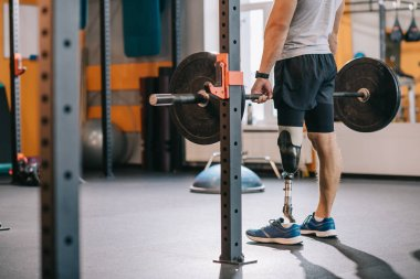 cropped shot of athletic sportsman with artificial leg working out with barbell at gym