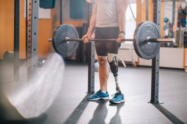 cropped shot of sportsman with artificial leg working out with barbell at gym