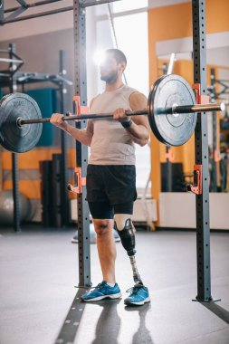 muscular young sportsman with artificial leg working out with barbell at gym