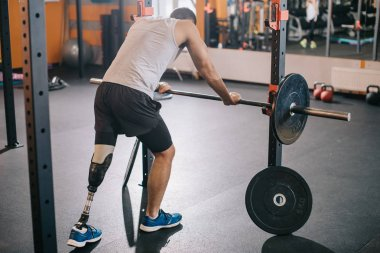 handsome young sportsman with artificial leg leaning on barbell at gym