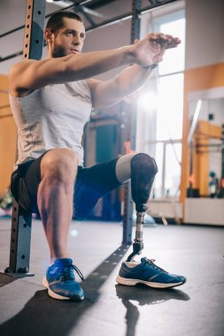 handsome young sportsman with artificial leg working out at gym
