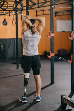 rear view of young sportsman with artificial leg stretching near gymnastics ladder at gym