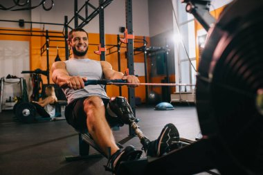 handsome young sportsman with artificial leg working out with rowing machine at gym