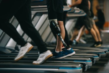 cropped shot of sportsman with artificial leg running on treadmill at gym with other people