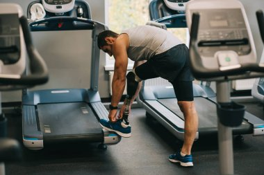 athletic young sportsman with artificial leg lacing up shoe at gym