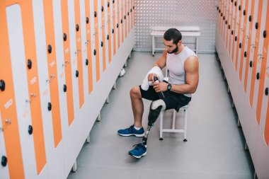 handsome young sportsman with artificial leg sitting on bench at gym changing room