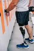 Oříznout záběr sportovce s umělou nohou otevření skříňky s elektrický klíč na zápěstí v šatně tělocvičny