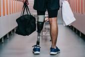 Oříznout záběr sportovce s umělou nohou stojí v šatně tělocvičny s ručníkem a pytel