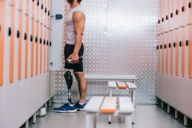 cropped shot of sportsman with artificial leg taking stuff from gym locker