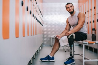 smiling young sportsman with artificial leg sitting on bench at gym changing room and using smartphone