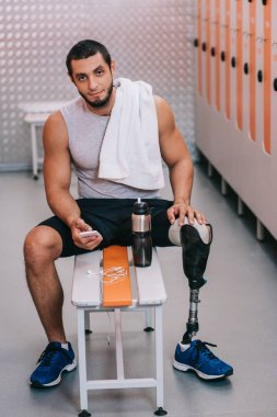 handsome young sportsman with artificial leg sitting on bench at gym changing room and using smartphone