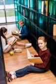 vysoký úhel pohledu rozkošný školák knihu a usmívá se na kameru při čtení se spolužáky v knihovně