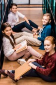 Fotografie high angle view of schoolkids with books sitting on floor and smiling at camera in library