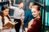 szép iskolás tartja a könyvet, és mosolyogva a kamera, míg a látogató függvénytár, az osztálytársaival