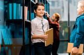 Fotografie Cute usmívající se školáci drží knihy při studiu v knihovně