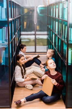 high angle view of adorable schoolkids reading books on floor in library