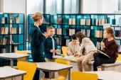 mladé samice knihovník držel pohár a při pohledu na schoolkids čtení knih v knihovně