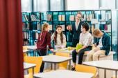 mladé ženy knihovnice drží pohár a při pohledu na usmívající se školáci v knihovně