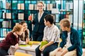 Fotografie mladé samice knihovník držel pohár a při pohledu na usmívající se schoolkids v knihovně