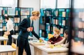 mladá žena učitel drží pohár a při pohledu na školačky studovat v knihovně