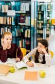 školačky psaní s tužky při studiu v knihovně