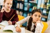 roztomilé školačky psaní s tužky a koukal při studiu v knihovně