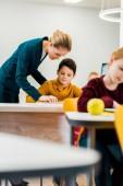 mladá žena učitel pomáhá žáků studovat na stoly