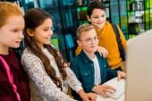 aranyos boldog schoolkids asztali számítógépes könyvtári