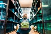 zadní pohled na chlapce s batohem sedí na podlaze v knihovně