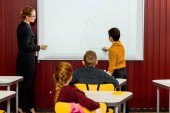 Fotografie zadní pohled na schoolkids a učitel studoval s interaktivní tabule za