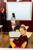vysoký úhel pohledu rozkošný školák se usmívá na kameru spolužáky a učitel studoval u tabule za