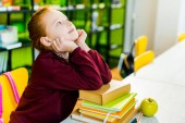 Fotografie adorable schoolgirl sitting at desk with books and looking up in library
