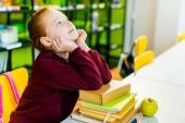 Fényképek aranyos iskoláslány ülő-on iskolapad-könyvek, és felnézett a könyvtár